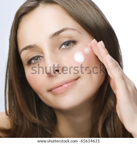 Beautiful Young Woman applying facial moisturizing cream.Skincare concept - stock photo