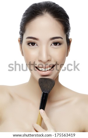 Beautiful young woman applying foundation powder or blush with makeup brush. Isolated on white background.-Studio Shot