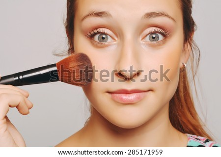 Beautiful young woman applying make up with brush. Make-up concept. - stock photo