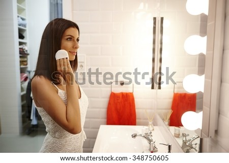 Beautiful young woman applying makeup in bathroom.