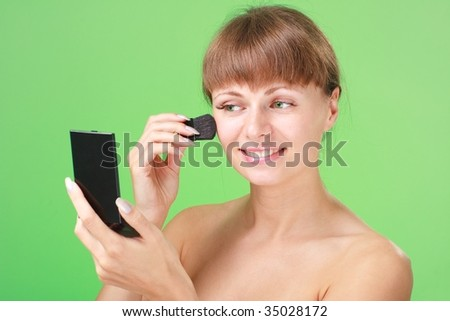 Beautiful young woman applying makeup on a green background.