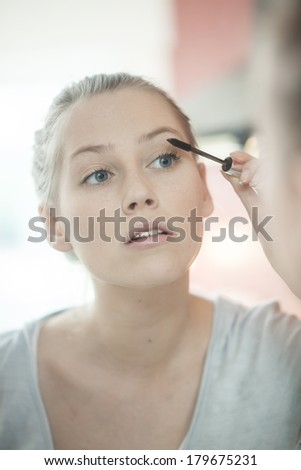 beautiful young woman applying makeup on her eyelashes in front of her mirror - stock photo