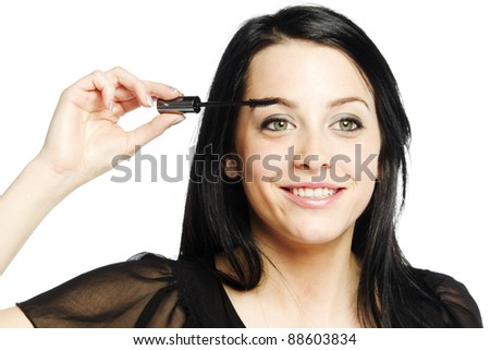 Beautiful young woman applying mascara on eye lashes smiling - stock photo