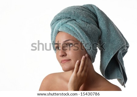 Beautiful young woman applying moisturizer to her skin after shower