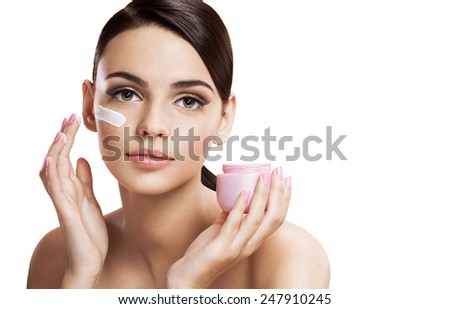 Beautiful young woman applying moisturizing creme, skin care concept / photo composition of brunette girl  - isolated on white background  - stock photo