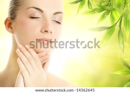 Beautiful young woman applying organic cosmetics to her skin - stock photo