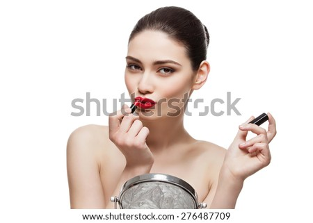 Beautiful young woman applying red lipstick in front of table mirror. Isoalted over white background. Copy space. - stock photo