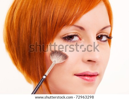 beautiful young woman applying rouge on her face