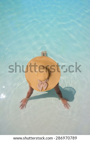 Beautiful young woman at a pool of a luxurious hotel  - stock photo