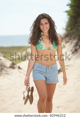Beautiful young woman at beach in summer nature - stock photo