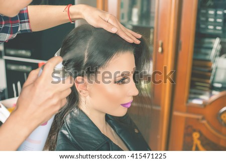 Beautiful young woman at beauty salon. Fashion hairstyle. Make up. Hair saloon. Hairdresser using hair spray
