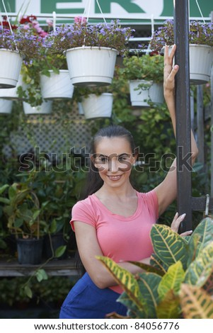 Beautiful young woman at garden store in front of hanging plants.