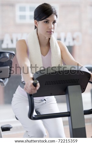 Beautiful young woman at gym, doing biking exercises - stock photo