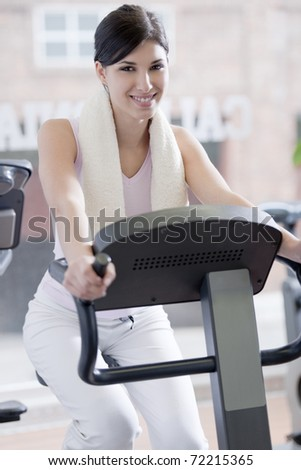 Beautiful young woman at gym, doing biking exercises - stock photo
