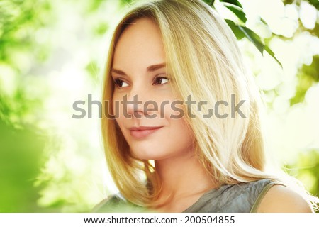 Beautiful young woman at summertime. Blonde hair. Dreamy smile. Close up portrait. Beautiful sunlight. Blurred bokeh background.