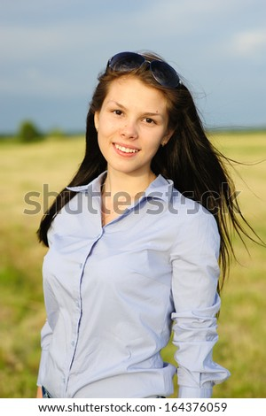 beautiful young woman at sunset in the field