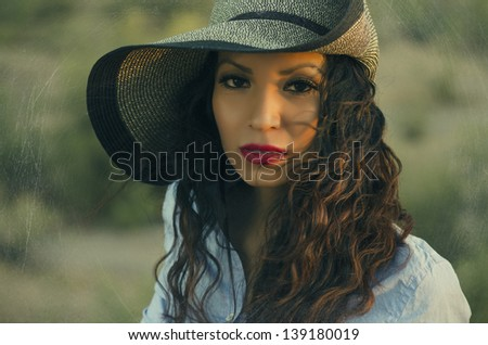 Beautiful young woman at sunset wind blowing her gorgeous hair. - stock photo