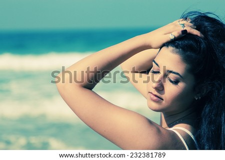 Beautiful young woman at the beach - stock photo
