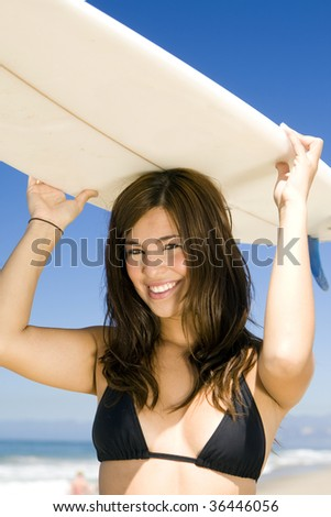 Beautiful young woman at the beach with surfboard - stock photo