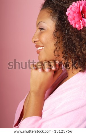 Beautiful young woman at the spa in a robe on pink background - stock photo