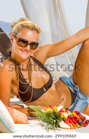 Beautiful young woman at the summer lounge eating a fruit salad - stock photo