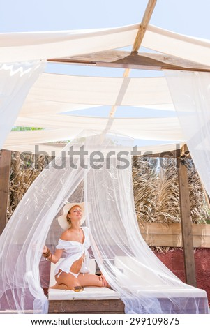 Beautiful young woman at the summer lounge under white veil - stock photo