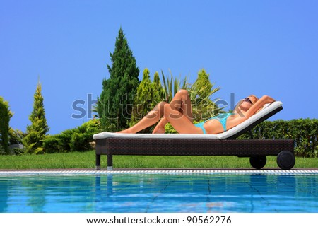 Beautiful young woman at the swimming pool in her private villa - stock photo