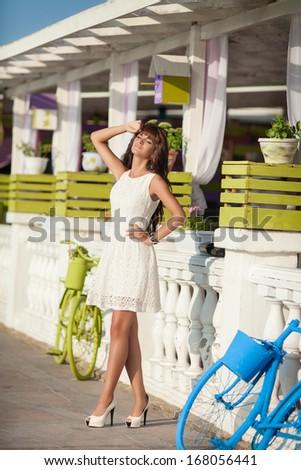 Beautiful young woman at vacation walking outdoors near cafe. France. Monte carlo. Happy girl posing at street. Santorini - stock photo