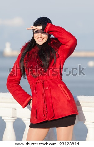 Beautiful young woman at winter. Attractive brunette in red looks, covering his eyes with his hand - stock photo