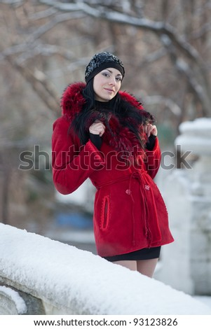 Beautiful young woman at winter. Young beautiful brunette in red standing in the winter park looking at camera smiling - stock photo