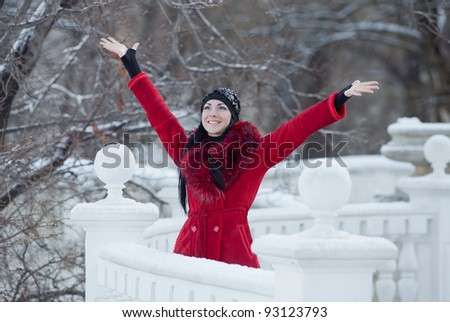 Beautiful young woman at winter. Young beautiful brunette in red standing in the winter park with arms raised looking up - stock photo