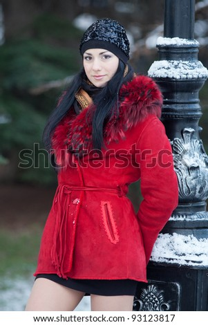 Beautiful young woman at winter. Young beautiful brunette standing near the column, wearing hat, winter time - stock photo