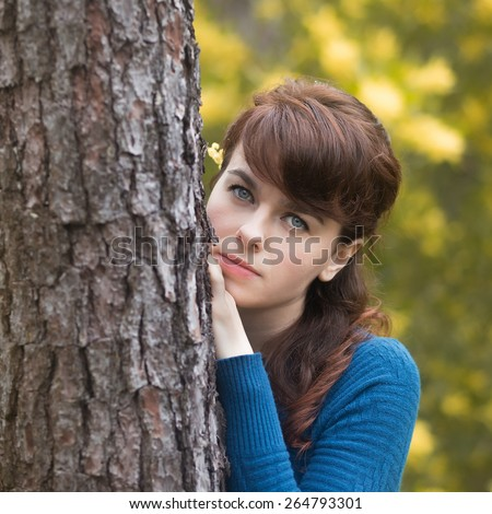 Beautiful young woman behind a tree