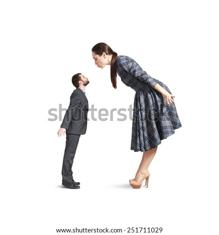 beautiful young woman bending forward and kissing small man. isolated on white background - stock photo
