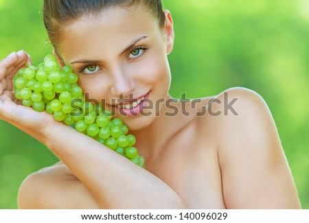 Beautiful young woman bites off from grape bunches, against summer green park. - stock photo