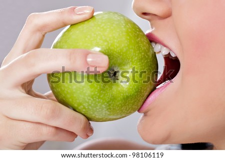 beautiful young woman biting a fresh green apple.