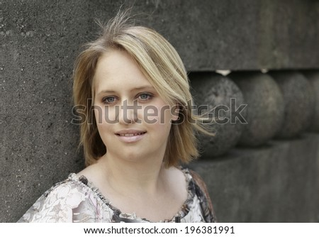beautiful young woman blond smiling by the concrete fence
