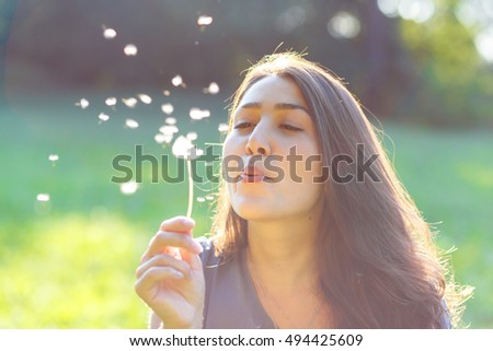 Beautiful young woman blowing a dandelion in park.