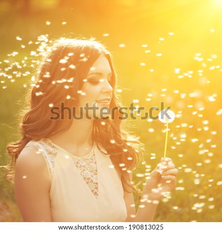 Beautiful young woman blowing a dandelion. Trendy young girl at sunset with flower - stock photo