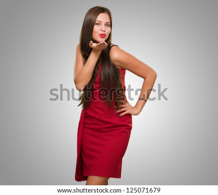 Beautiful Young Woman Blowing A Kiss against a grey background - stock photo