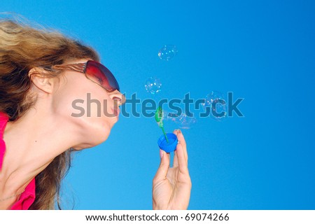 beautiful young woman blowing bubbles in the sky