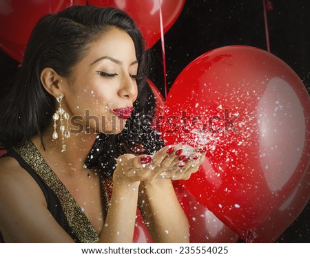 Beautiful young woman blowing confetti out of hands - stock photo