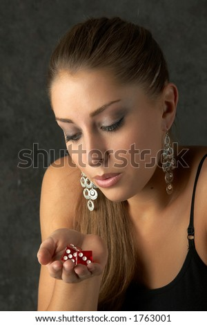 Beautiful Young Woman Blowing Dice - stock photo