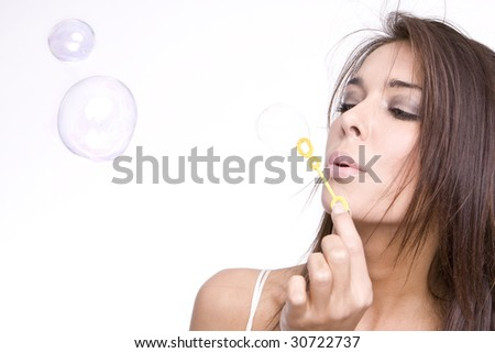 Beautiful young woman blowing soap bubbles - stock photo