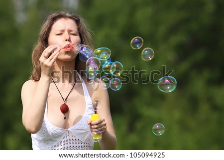 Beautiful young woman blowing soap bubbles outdoors