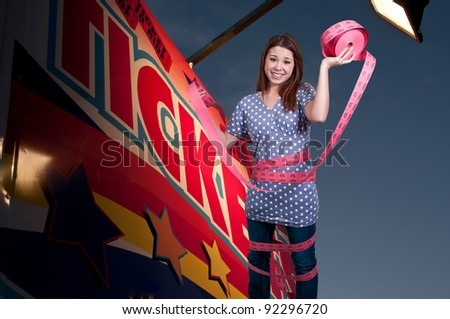 Beautiful young woman box office employee wrapped in admission tickets - stock photo