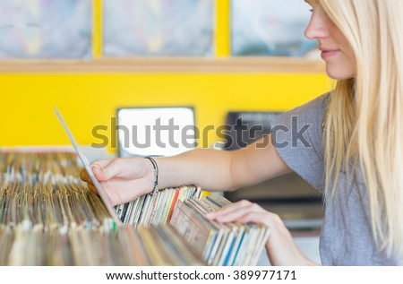 Beautiful young woman browsing vintage records in the vinyl store. - stock photo