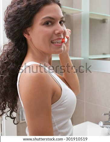 Beautiful young woman brushing her teeth in a home bathroom turning to smile at camera, home interior. Wellness, well being and healthy dental care lifestyle. Girl grooming indoors, morning routine. - stock photo