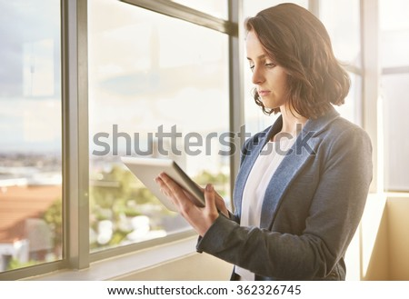 Beautiful young woman business entrepreneur standing in her office with sunflare and looking like a confident corporate leader using a modern digital tablet - stock photo