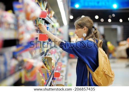 Beautiful young woman buying food at supermarket